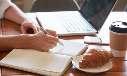 closeup-breakfast-table-with-female-hands-putting-down-information-daily-planner_1098-20088